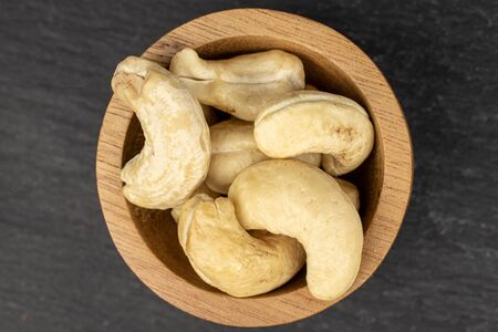 Lot of whole brown nut cashew in bamboo bowl flatlay on grey stone Stok Fotoğraf