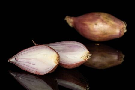 Group of one whole two halves of fresh brown shallot isolated on black glass