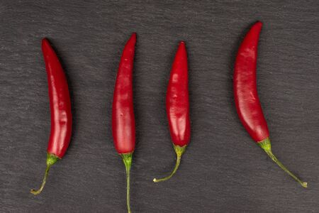 Group of four whole hot red chili cayenne flatlay on grey stone