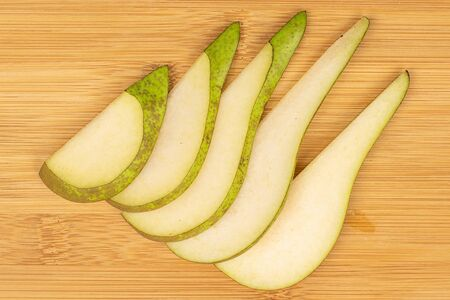 Group of five slices of fresh green pear flatlay on light wood