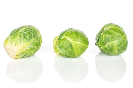 Group of three whole fresh green brussels sprout isolated on white background
