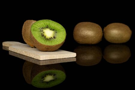 Group of two whole two halves of exotic brown kiwi on wooden cutting board isolated on black glass