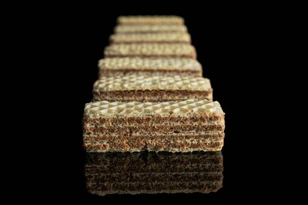 Group of seven whole crispy beige hazelnut wafer cookie isolated on black glass Stock Photo