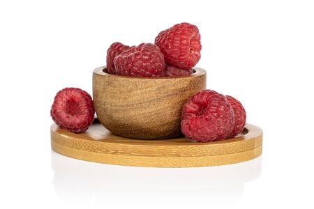 Lot of whole fresh red raspberry on round bamboo coaster in bamboo bowl isolated on white background