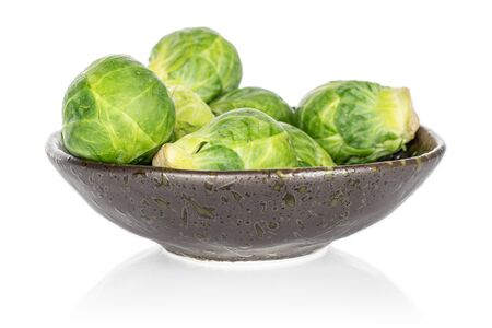 Group of six whole fresh green brussels sprout on glazed bowl isolated on white background