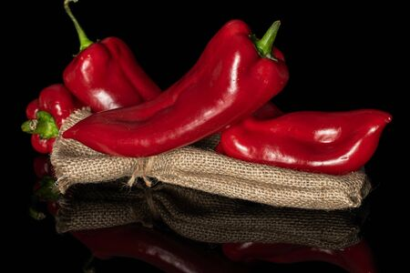 Group of four whole sweet red bell pepper with jute bag isolated on black glass Stok Fotoğraf