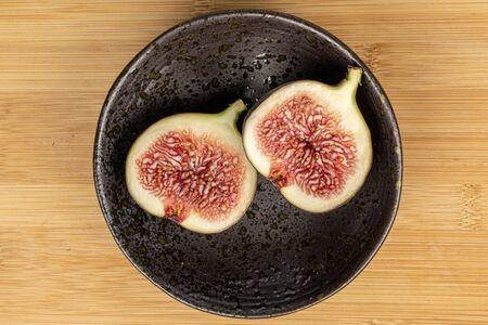 Group of two halves of sweet purple fig on glazed bowl flatlay on light wood Zdjęcie Seryjne