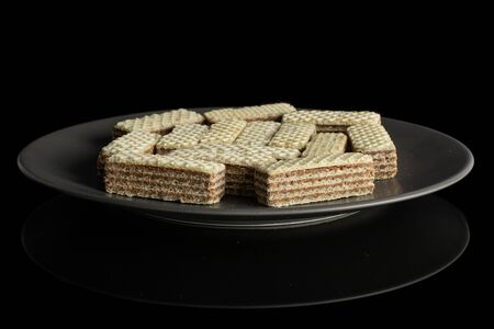 Lot of whole crispy beige hazelnut wafer cookie on gray ceramic plate isolated on black glass 写真素材
