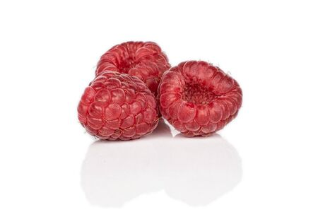 Group of three whole fresh red raspberry isolated on white background