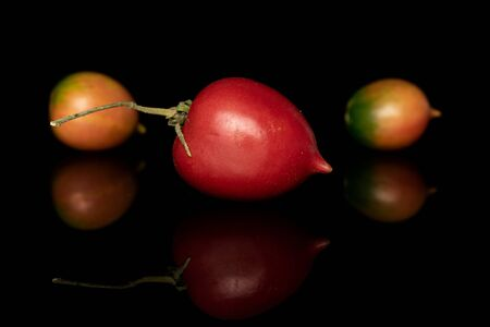 Group of three whole fresh tomato de barao one with stem isolated on black glass