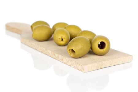 Group of eight whole marinated green olive on wooden cutting board isolated on white background
