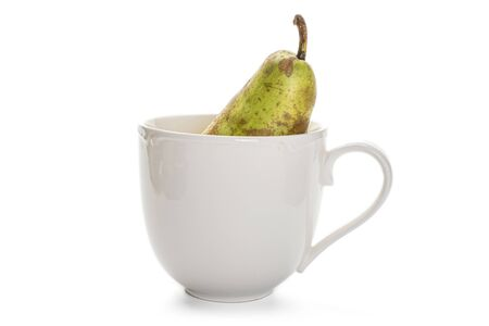 One whole fresh green pear conference in porcelain cup isolated on white background 写真素材