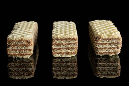 Group of three whole crispy beige hazelnut wafer cookie in row isolated on black glass 写真素材