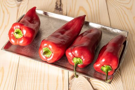 Group of four whole sweet red bell pepper on tray on natural wood