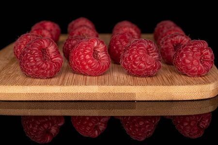 Lot of whole arranged fresh red raspberry on bamboo cutting board isolated on black glass