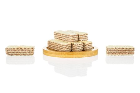 Group of seven whole crispy beige hazelnut wafer cookie on bamboo coaster isolated on white background