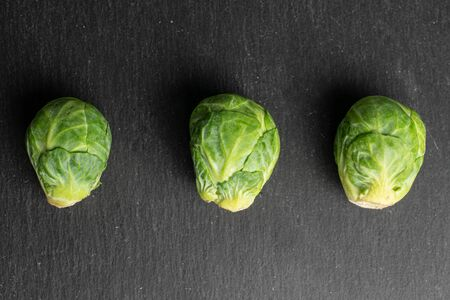 Group of three whole fresh green brussels sprout flatlay on grey stone