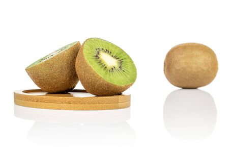 Group of one whole two halves of exotic brown kiwi on round bamboo coaster isolated on white background