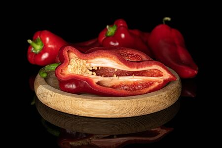 Group of three whole one half of sweet red bell pepper on bamboo plate isolated on black glass Stok Fotoğraf