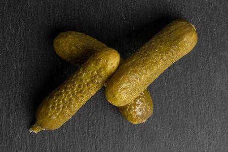 Group of three whole sour green pickle flatlay on grey stone Zdjęcie Seryjne