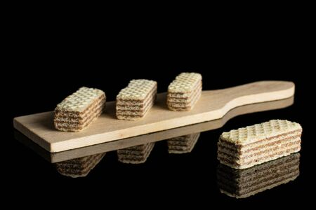 Group of four whole crispy beige hazelnut wafer cookie on small wooden cutting board isolated on black glass 写真素材