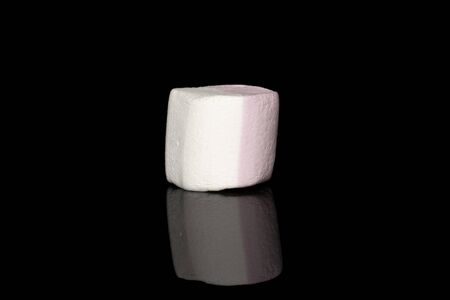 One whole sweet pastel marshmallow isolated on black glass