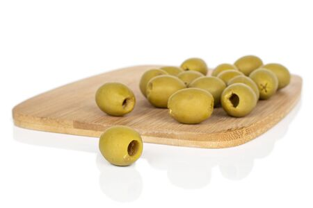 Lot of whole marinated green olive on bamboo cutting board isolated on white background 스톡 콘텐츠