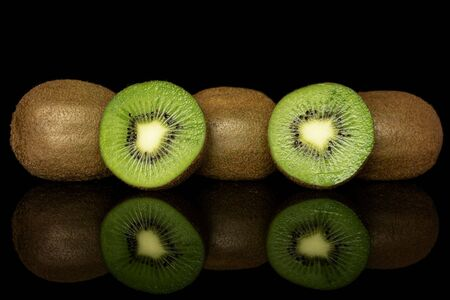 Group of three whole two halves of exotic brown kiwi isolated on black glass Reklamní fotografie