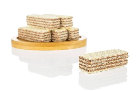 Group of six whole crispy beige hazelnut wafer cookie on bamboo coaster isolated on white background