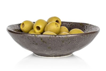 Lot of whole marinated green olive on glazed bowl isolated on white background 스톡 콘텐츠