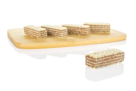 Group of five whole crispy beige hazelnut wafer cookie on bamboo cutting board isolated on white background 写真素材