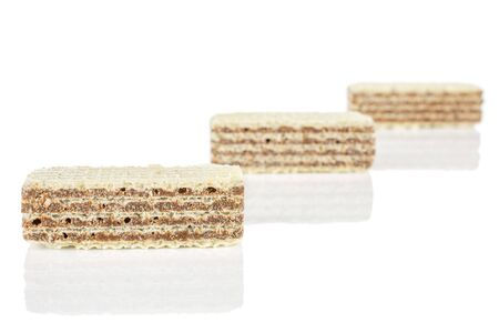 Group of three whole crispy beige hazelnut wafer cookie placed diagonally isolated on white background