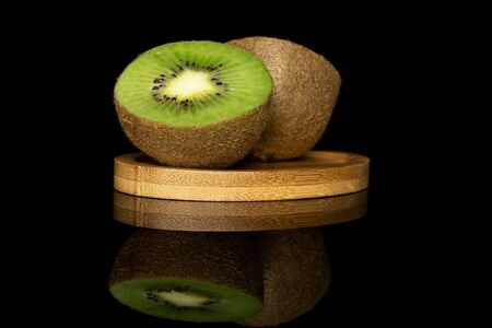 Group of two halves of exotic brown kiwi on round bamboo coaster isolated on black glass