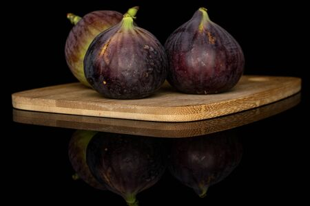 Group of three whole sweet purple fig on bamboo cutting board isolated on black glass