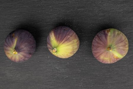 Group of three whole sweet purple fig flatlay on grey stone Reklamní fotografie