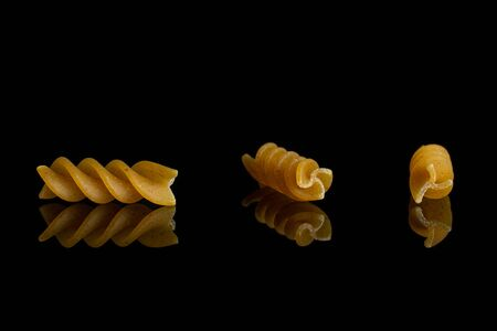 Group of three whole dry brown wholegrain fusilli isolated on black glass