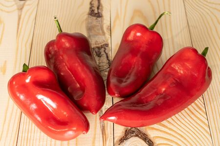 Group of four whole sweet red bell pepper on natural wood