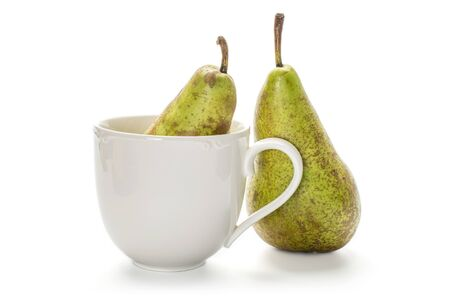Group of two whole fresh green pear conference in porcelain cup isolated on white background