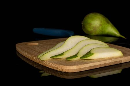Group of one whole five slices of fresh green pear on bamboo cutting board with steel knife isolated on black glass Reklamní fotografie