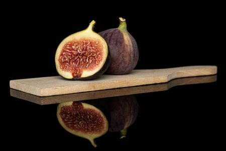 Group of one whole one half of sweet purple fig on wooden cutting board isolated on black glass Reklamní fotografie