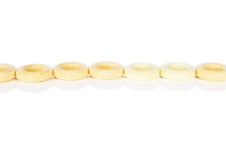Lot of whole round pale yellow candy in line isolated on white background Banco de Imagens
