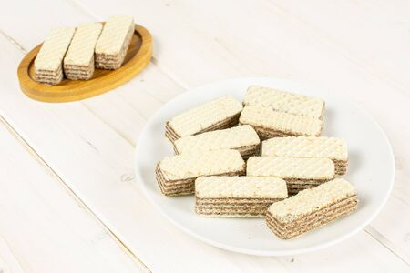 Lot of whole crispy beige hazelnut wafer cookie on bamboo coaster on white ceramic plate on white wood