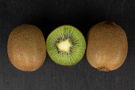 Group of two whole one half of exotic brown kiwi flatlay on grey stone Reklamní fotografie