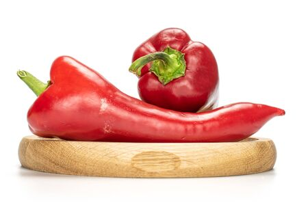 Group of two whole sweet red bell pepper on bamboo plate isolated on white background