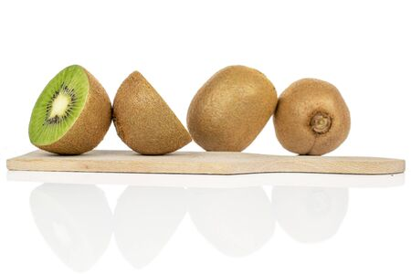 Group of two whole two halves of exotic brown kiwi on wooden cutting board isolated on white background