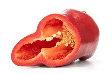 One half of sweet red bell pepper with seeds isolated on white background