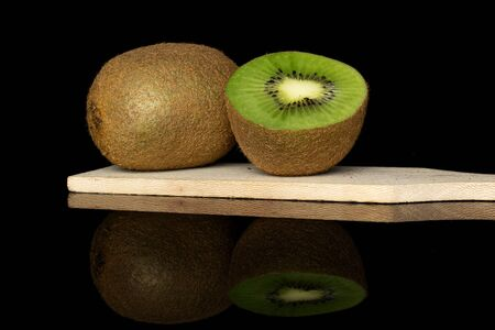 Group of one whole one half of exotic brown kiwi on wooden cutting board isolated on black glass