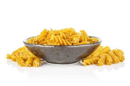 Lot of whole dry brown wholegrain fusilli in dark ceramic bowl isolated on white background 스톡 콘텐츠 - 131952967