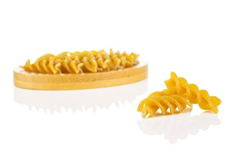 Lot of whole dry brown wholegrain fusilli two are aside and the rest is on bamboo coaster isolated on white background