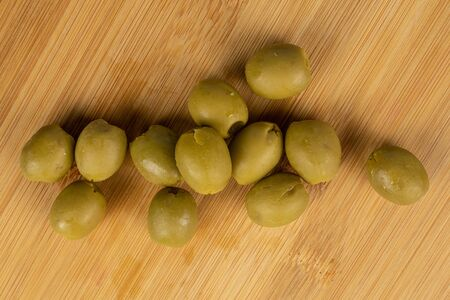 Lot of whole marinated green olive flatlay on light wood 스톡 콘텐츠 - 131953460